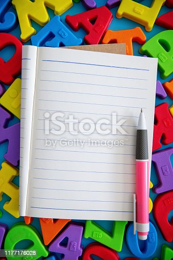 613303142 istock photo Lined paper notebook on multi colored alphabets blocks background 1177176028