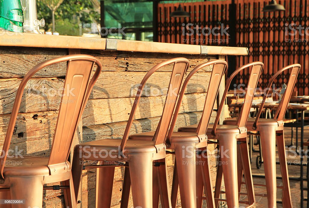 Lined up of metal bar stools stock photo