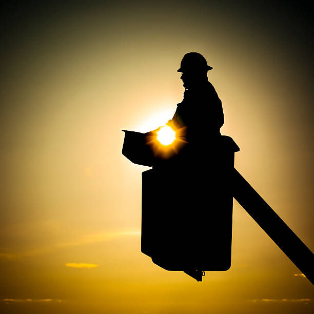 A lineman in a cherry picker backlit by the sunset stock photo
