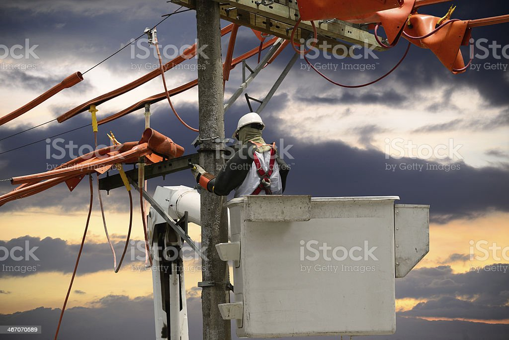 Lineman in cherry picker working on the telephone pole stock photo