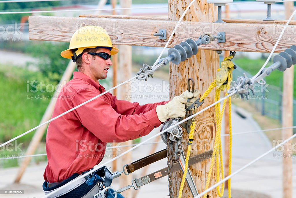 A lineman that is working on a pole stock photo