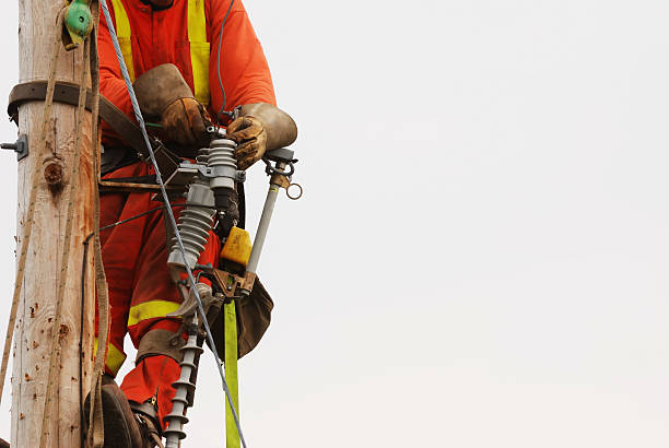 Lineman Up a pole fixing the wires. stock photo