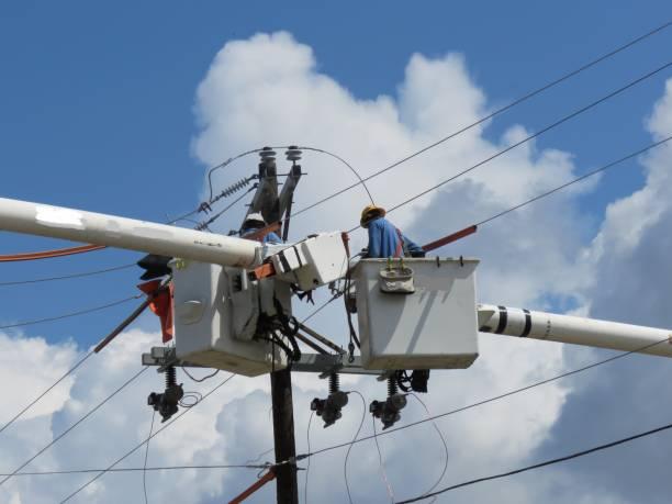 linemen im dienstprogramm lkw arbeiten an elektrischen anlagen - stromkabel stock-fotos und bilder