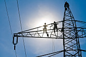 Two lineman on a power pylon for mounting. In the background blue sky and sun.