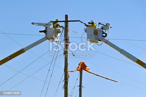 Linemen in bucket trucks working on electric power lines; dangerous occupations.