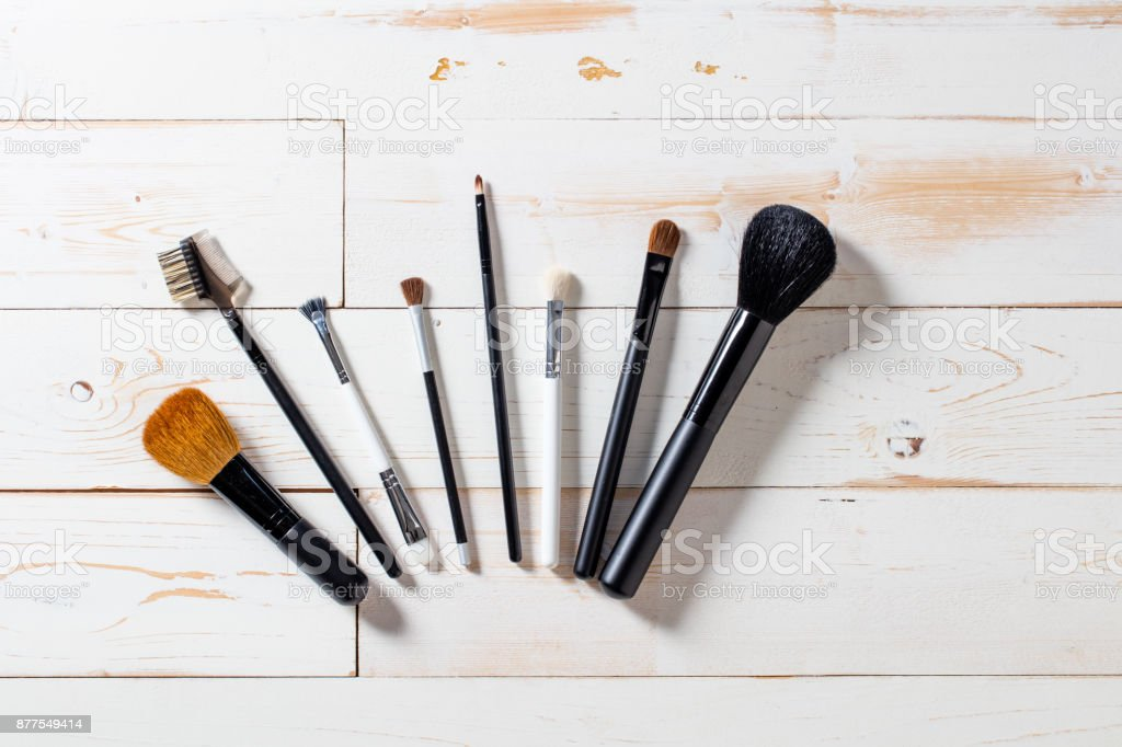 Lineup of artist makeup accessories with eyeshadow and blush brushes stock photo