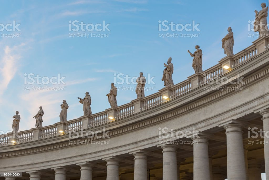 lineup of roman statues at St Peter's square in Rome Italy on gallery with pillars stock photo