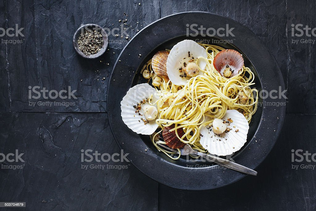 Linguine pasta with scallops Linguine pasta with scallops in garlic and parsley sauce. Animal Shell Stock Photo