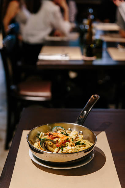 linguine seafood: linguine med räkor, squids, musslor kokta i olivolja, chili och vitlök. serveras i rostfri kruka på pappers matta. - pasta vongole bildbanksfoton och bilder