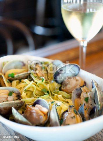 A large bowl of linguine with clams served with a glass of wine