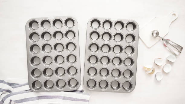 Lining cupcake pan with paper cupcake liners. Flat lay. Lining cupcake pan with paper cupcake liners. muffin tin stock pictures, royalty-free photos & images