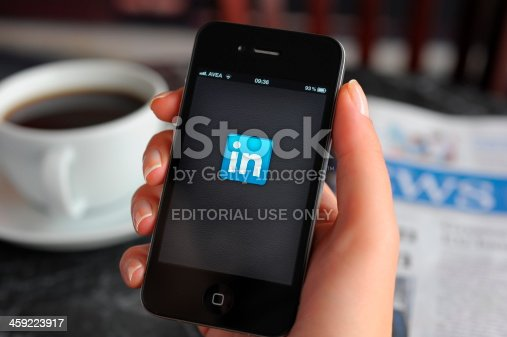 Astanbul, Turkey - December 14, 2011: Woman hand holding an touching an Apple iPhone 4 in a coffee shop. iPhone 4 displaying start up screen of LinkedIn application. The iPhone 4 is a touchscreen slate smartphone and the fourth generation iPhone, developed by Apple Inc.