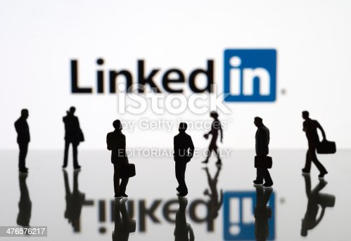 İstanbul, Turkey - February 12, 2014: Human figurines standing in front of Apple iPad monitor displaying LinkedIn logo. LinkedIn is a social networking service for people in professional occupations.