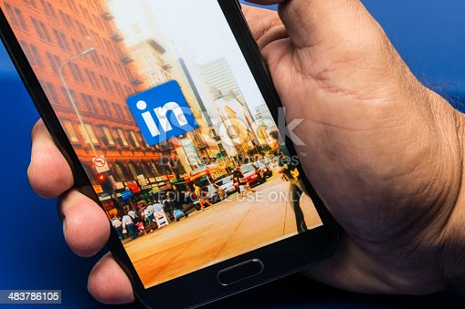 Miami, Florida, USA- May 27, 2013: Linkedin, Man hand holding a samsung note II smart phone showing the Linkedin application web page on blue background. Linkedin is a business oriented social networking site where is it possible to show own skills and contacts.