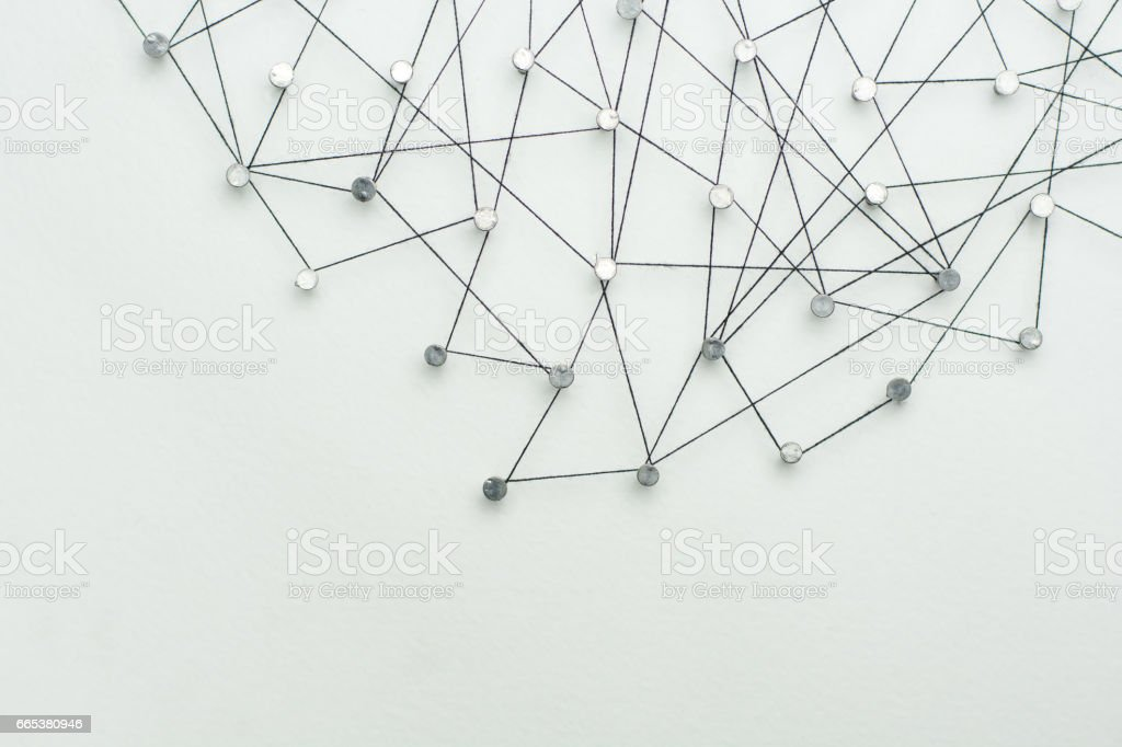 Linking entities. Network, networking, social media, internet communication abstract. A small network connected to a larger network. in paper linked together by cotton with a black tint stock photo