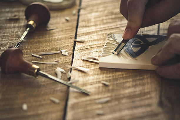 Linocut carving A photo of a hand cutting a design in rubber. linocut stock pictures, royalty-free photos & images