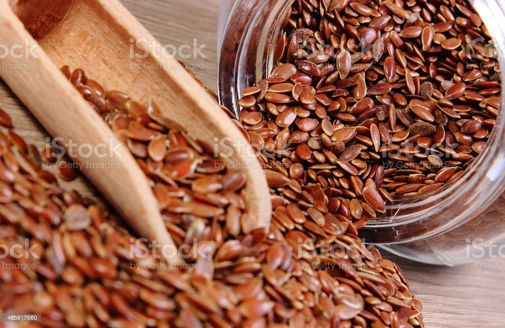 Linseed spilling out of jar on wooden background stock photo