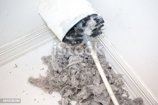 Dryer vent in a home being cleaned out with a round brush. There is a large pile of lint that has been removed from the vent on a white tiled floor. The walls and baseboards are white. The lint is gray. Taken with a Canon 5D Mark 3 camera.  rm