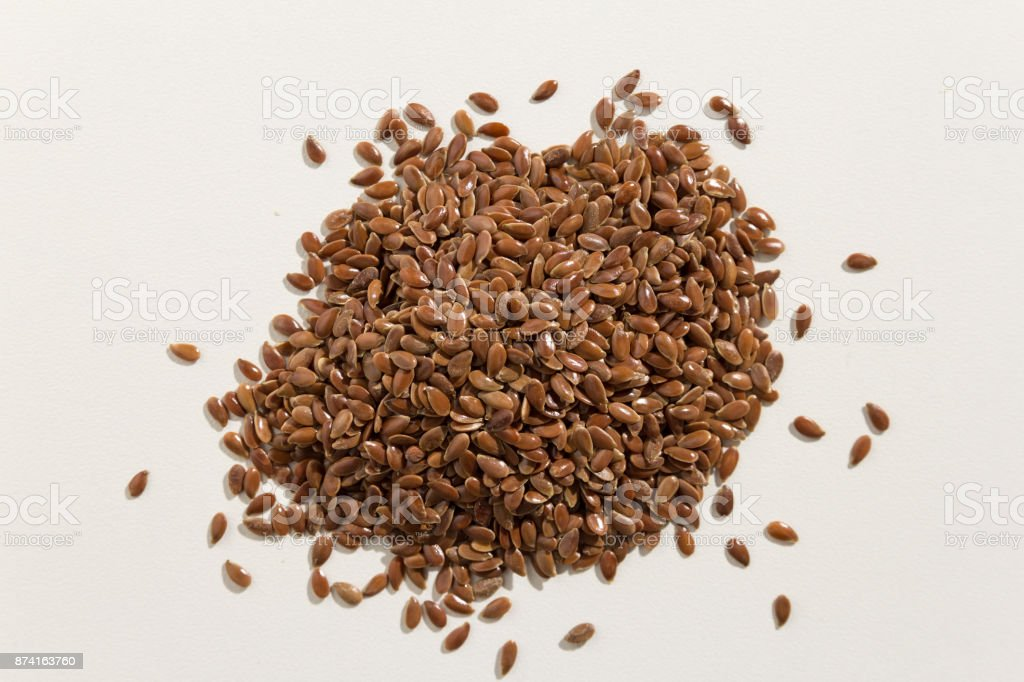 Linum usitatissimum is scientific name of Brown Flax seed. Also known as Linseed, Flaxseed and Common Flax. Pile of grains, isolated white background. Pile of grains. Top view. stock photo