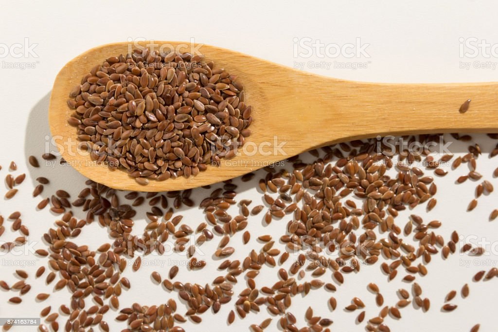 Linum usitatissimum is scientific name of Brown Flax seed. Also known as Linseed, Flaxseed and Common Flax. Pile of grains, isolated white background. Healthy grains on a wooden spoon. White background. stock photo