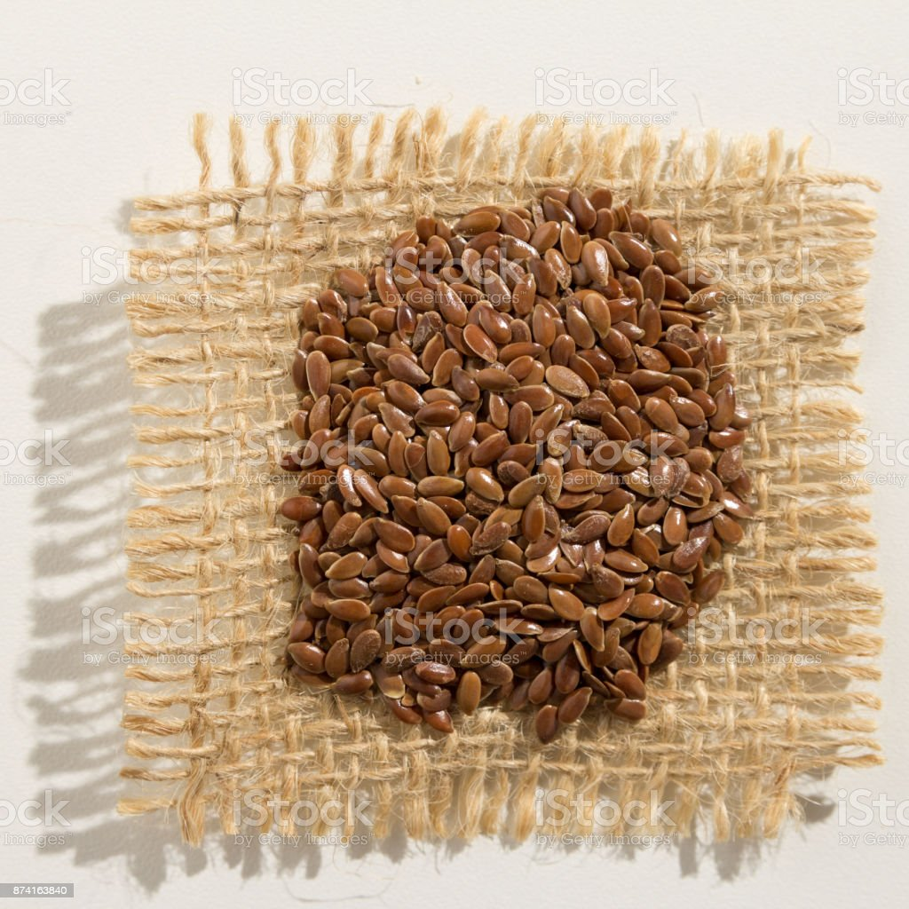 Linum usitatissimum is scientific name of Brown Flax seed. Also known as Linseed, Flaxseed and Common Flax. Pile of grains, isolated white background. Close up of grains over burlap. stock photo