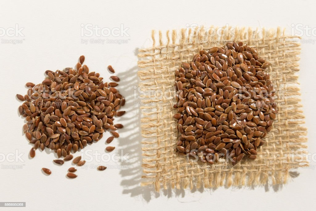 Linum usitatissimum is scientific name of Brown Flax seed. Also known as Linseed, Flaxseed and Common Flax. Pile of grains, isolated white background. Close up of grains spreaded over white table. stock photo