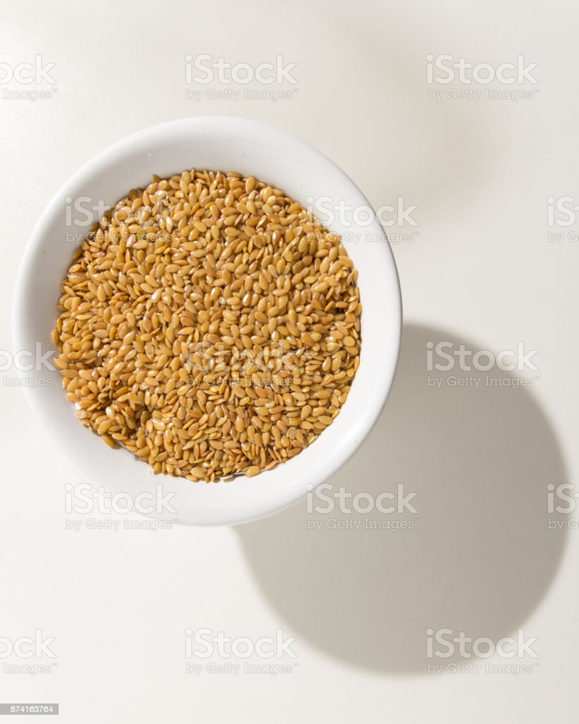 Linum usitatissimum is scientific name of Golden Flax seed. Also known as Linseed, Flaxseed and Common Flax. Pile of grains, isolated white background. Grains in a bowl. Shadow over white table. stock photo