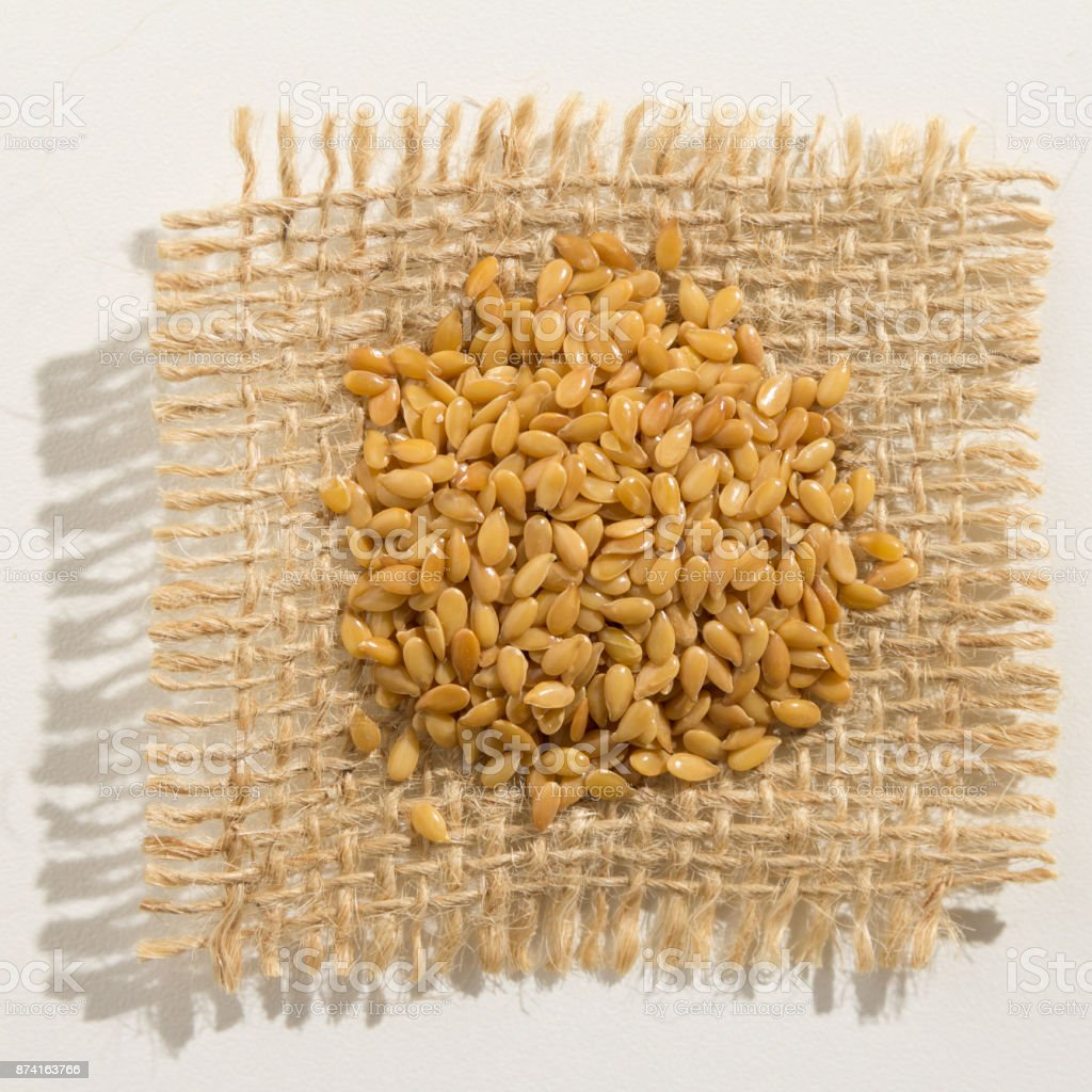 Linum usitatissimum is scientific name of Golden Flax seed. Also known as Linseed, Flaxseed and Common Flax. Pile of grains, isolated white background. Close up of grains over burlap. stock photo
