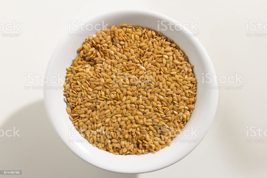 Linum usitatissimum is scientific name of Golden Flax seed. Also known as Linseed, Flaxseed and Common Flax. Pile of grains, isolated white background. Top view of grains in a bowl. White background. stock photo