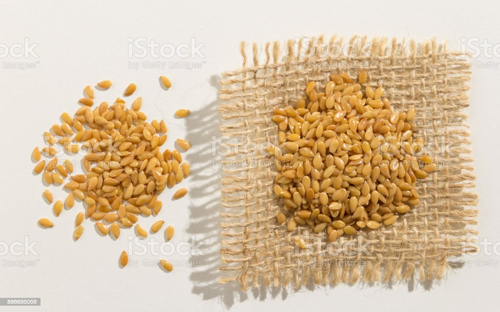 Linum usitatissimum is scientific name of Golden Flax seed. Also known as Linseed, Flaxseed and Common Flax. Pile of grains, isolated white background. Close up of grains spreaded over white table. stock photo