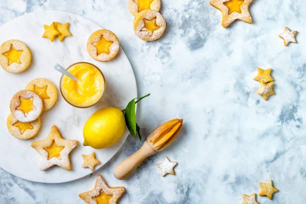 Linzer Weihnachtsplätzchen gefüllt mit Zitronenquark und mit Zucker auf weißem Marmorbrett gestaubt – Foto