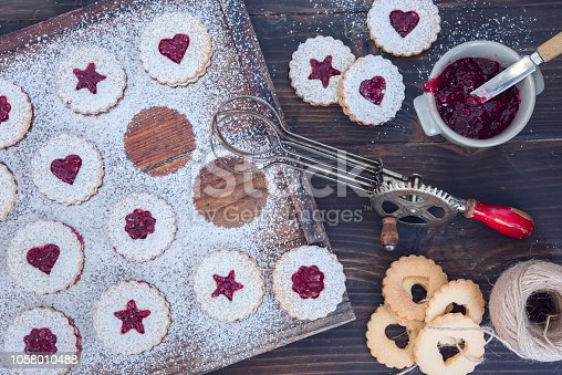 istock Linzer Christmas cookies with jam and powder sugar flat lay and copy space. Creative concept. 1058010488
