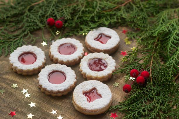 linzer kekse in eine weihnachtsdekoration auf eine holzoberfläche. - aufstrich weihnachten stock-fotos und bilder