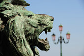 Ancient statue head in profile. Street light from Venice in background.