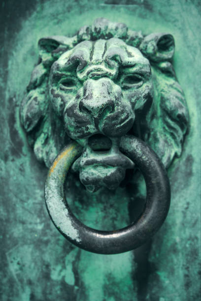Lion Crypt Door Handle A close up of a very old and weathered liod head door handle on a crypt. sdominick stock pictures, royalty-free photos & images