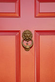 A lion head door knocker made from brass stands guard on this bright red door.