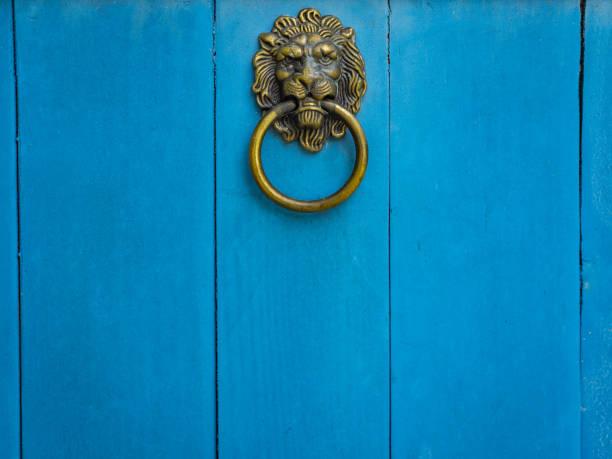 사자 머리 문 블루 나무 문을 두 들기는 사람. - 노커 뉴스 사진 이미지