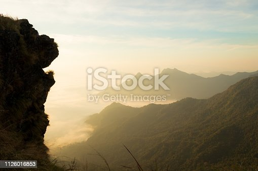 lion head shaped huge cliff with fog and mountains in the morning at Chiang rai,Thailand