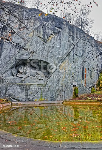 Lucerne, Switzerland - January 4, 2014: Dying Lion or Lion of Lucerne monument in Lucerne, Switzerland. Carved in the rock, it honors Swiss Guards, massacred during the French Revolution when revolutionaries stormed the Tuileries Palace