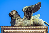 Lion statue at Piazza San Marco (St Mark`s Square), Venice, Italy. Winged lion is an ancient symbol and landmark of Venice. Renaissance architecture and art of Venice close-up.