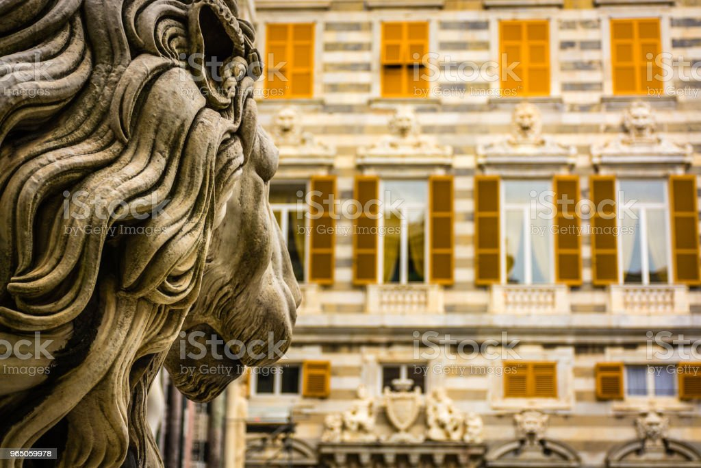 Lion statue looking towards old building zbiór zdjęć royalty-free