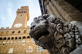 A lion statue at the Loggia dei Lanzi in Piazza della Signoria, Florence (Tuscany, Italy). On the background the Palazzo Vecchio's ancient tower by night.