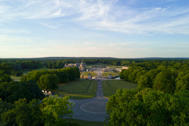 Carrefour des Lions in Chantilly (Oise) Chantilly, France - July 05 2017: Carrefour des Lions with in the background, the Chantilly castle surrounded by the woods. picardy stock pictures, royalty-free photos & images