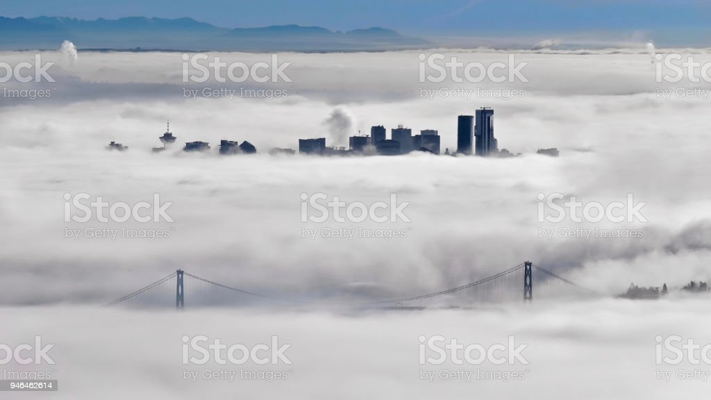 Lions Gate Bridge and Vancouver skyline in foggy morning in winter. stock photo