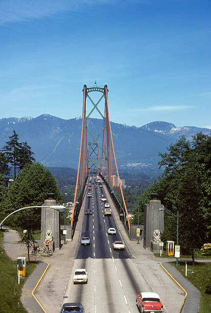 Lion's Gate Bridge, British Columbia, circa 1975 Lion's Gate Bridge in Vancouver, British Columbia. Lots of copy space in the sky, as well as period-specific cars from the mid-70s driving across the bridge. hearkencreative stock pictures, royalty-free photos & images