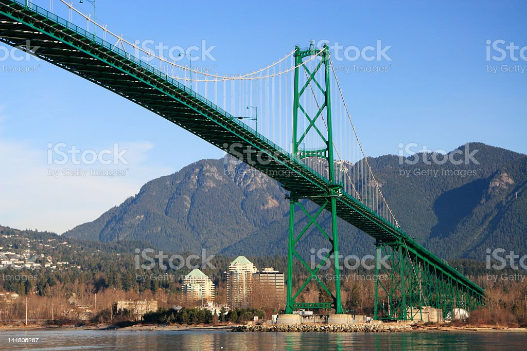 Lions Gate Bridge over water against a mountain range stock photo