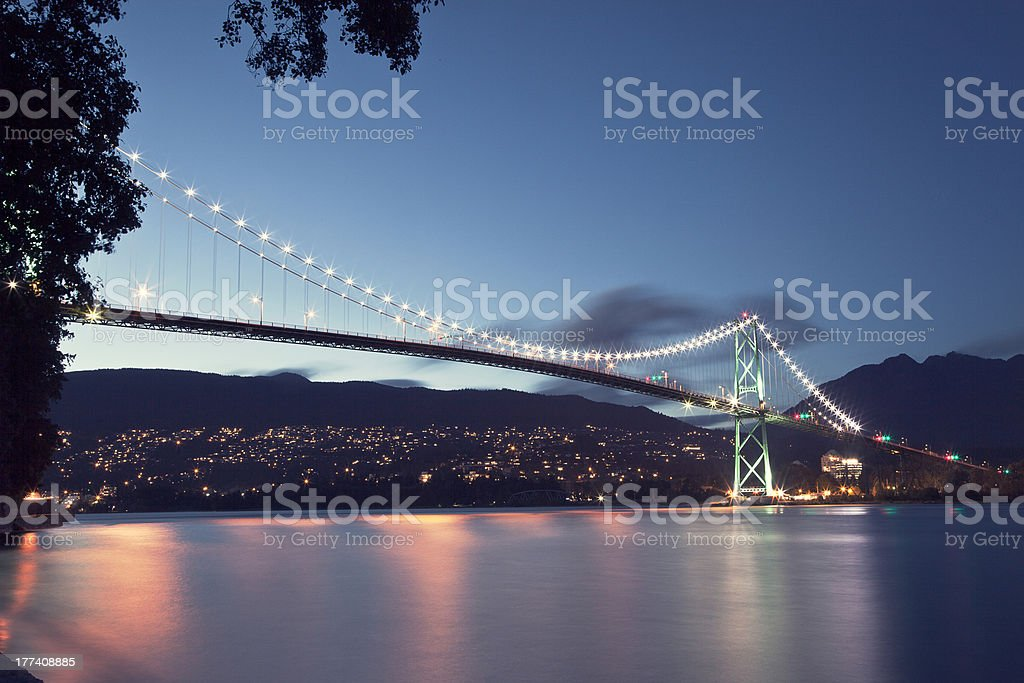 Lions gate bridge with lights on at night stock photo