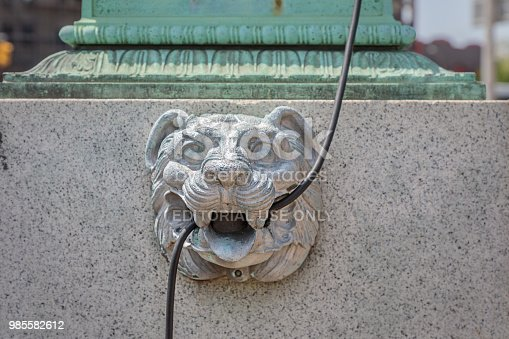 Grand Army Plaza, Brooklyn, New York, USA – May 9, 2018: Statue of a lions head utilized to hold a electric cable