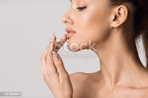 Lip augmentation. Beautiful girl touching her lips over gray background, copy space