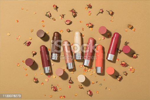 Lip balms with rose petals isolated on brown background (with clipping path)